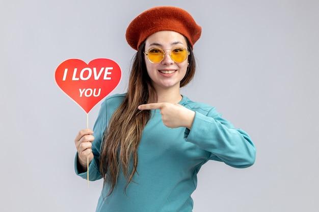 발렌타인 데이에 웃는 어린 소녀는 안경을 쓰고 모자를 쓰고 막대기에 빨간 하트를 가리키며 흰색 배경에 격리된 텍스트를 사랑합니다