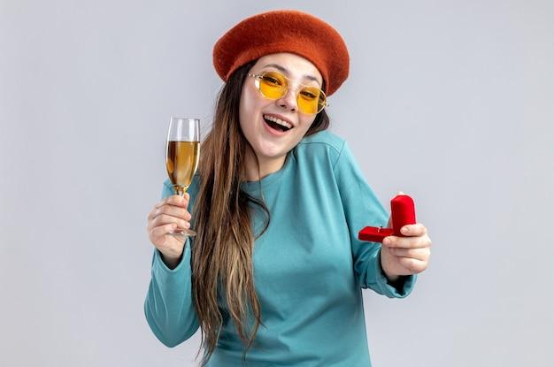 Улыбающаяся молодая девушка в день святого валентина в шляпе с бокалами и бокалом шампанского с обручальным кольцом на белом фоне