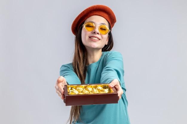 Улыбающаяся молодая девушка в день святого валентина в шляпе с очками, протягивая коробку конфет перед камерой, изолированной на белом фоне
