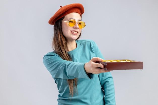 Улыбающаяся молодая девушка в день святого валентина в шляпе с очками, протягивая коробку конфет сбоку, изолированную на белом фоне
