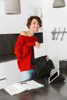집에서 대학에 가기 위해 그녀의 가방을 포장 웃는 어린 소녀