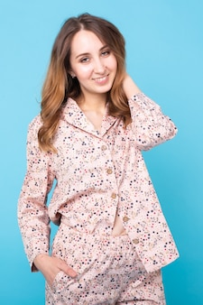 Smiling young girl in pajamas home wear posing while resting at home isolated on blue background