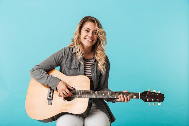 블루 이상 격리 앉아있는 동안 기타를 연주 웃는 어린 소녀