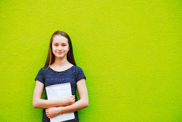 Smiling young girl posing with notepad