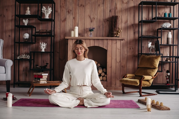 Smiling young girl practicing yoga sitting in lotus pose, meditating in cozy home interior. female training for wellness.