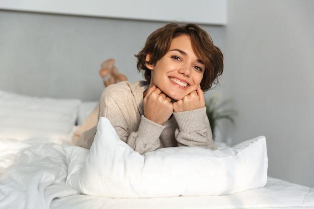 아침에 침대에서 편안 하 게 웃는 어린 소녀