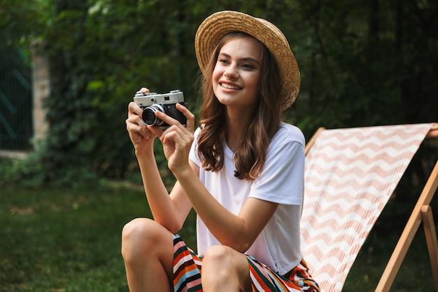 여름에 야외 도시 공원에서 해먹에 쉬고 웃는 어린 소녀, 사진 카메라로 사진을 찍고