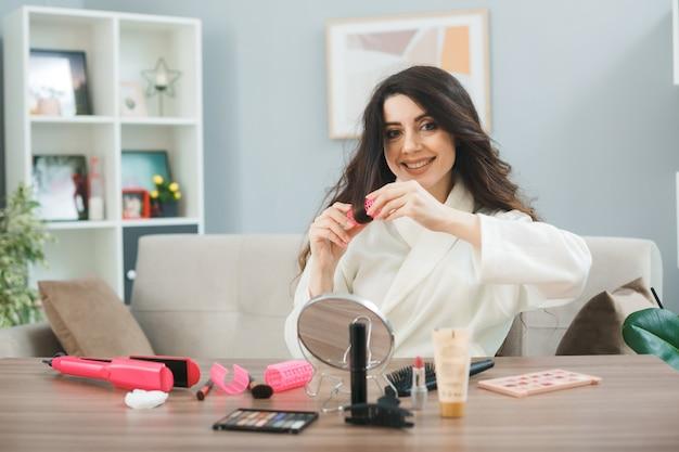 Улыбающаяся молодая девушка, сидящая за столом с инструментами для макияжа, накручивает волосы в бигуди в гостиной