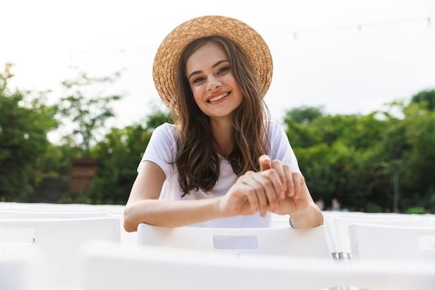 여름에 야외 도시 공원에 앉아 어린 소녀 미소