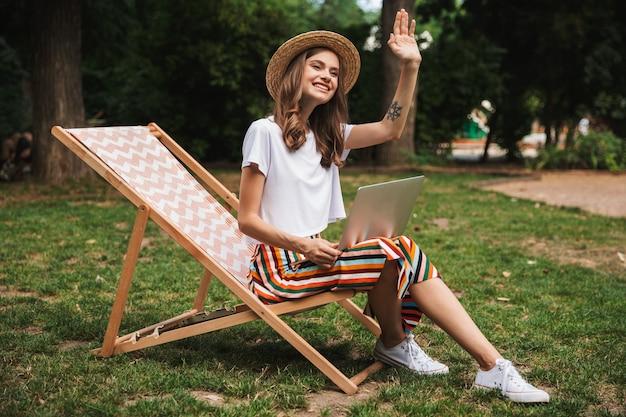 Улыбающаяся молодая девушка сидит с портативным компьютером в парке на открытом воздухе, размахивая