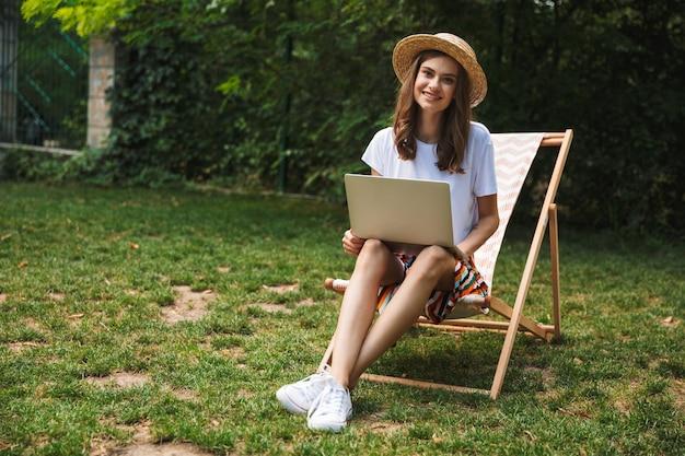 Улыбающаяся молодая девушка, сидящая с портативным компьютером в парке на открытом воздухе