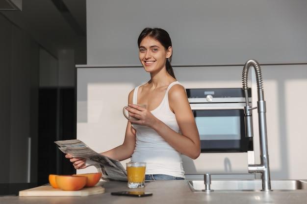 朝、台所に立って、新聞を読んで、お茶を飲む若い女の子の笑顔