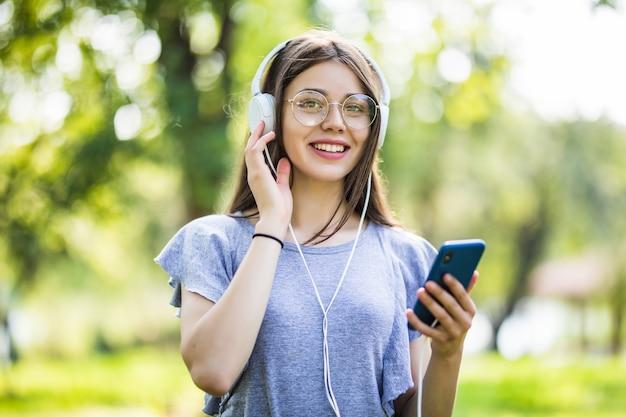 Улыбающаяся молодая девушка-студентка с рюкзаком держит мобильный телефон, гуляет в парке, слушает музыку в наушниках