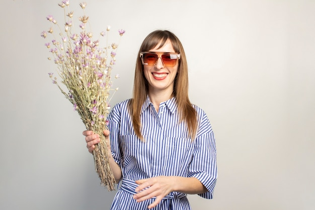 Smiling young girl in sunglasses holds a bouquet of wildflowers on a light background