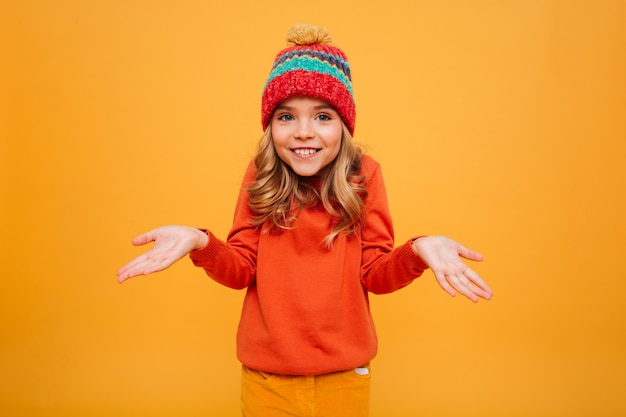 Smiling young girl in sweater and hat shrugs her shoulders and looking at the camera over orange