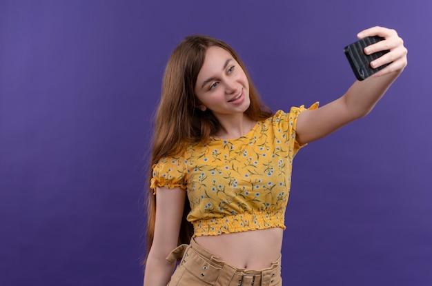 Ragazza sorridente che cattura selfie sulla parete viola isolata con lo spazio della copia