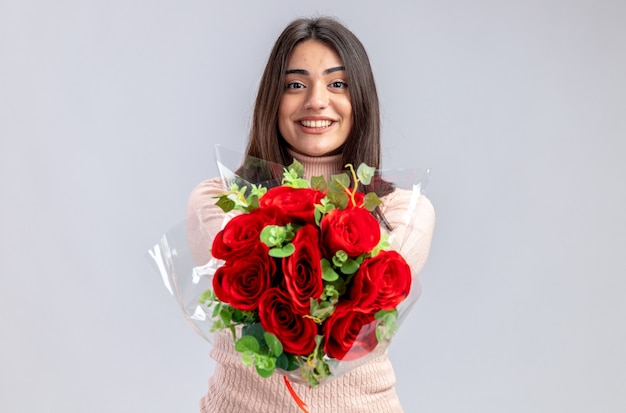 Smiling young girl on valentines day holding out bouquet at camera isolated on white background