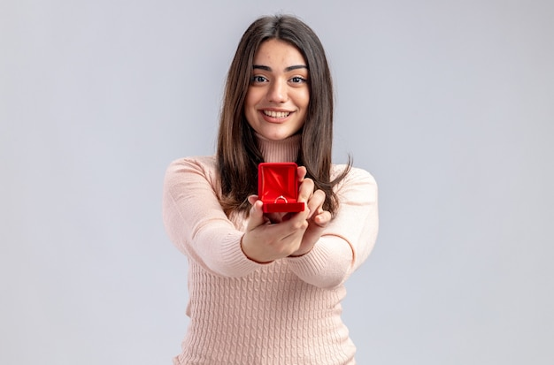 Smiling young girl on valentines day holding out wedding ring at camera isolated on white background