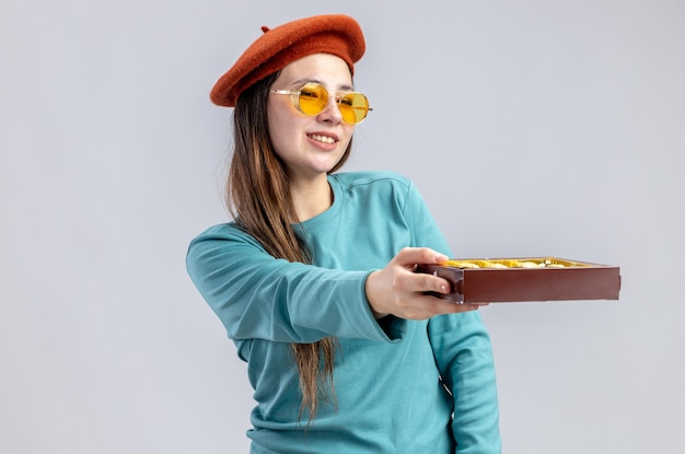 Sorridente ragazza il giorno di san valentino che indossa un cappello con gli occhiali tenendo fuori una scatola di caramelle a lato isolato su sfondo bianco on