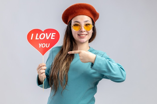 Smiling young girl on valentines day wearing hat with glasses holding and points at red heart on a stick with i love you text isolated on white background