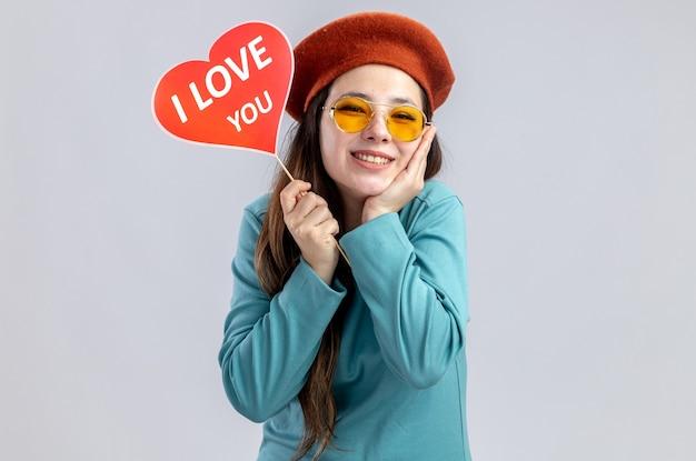 Sorridente ragazza il giorno di san valentino che indossa un cappello con gli occhiali che tiene cuore rosso su un bastone con ti amo testo mettendo la mano sulla guancia isolato su sfondo bianco