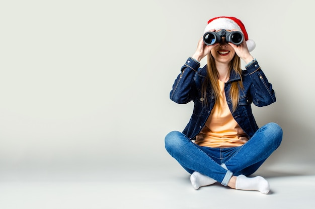 Улыбающаяся молодая девушка в шляпе санта-клауса на светлом фоне