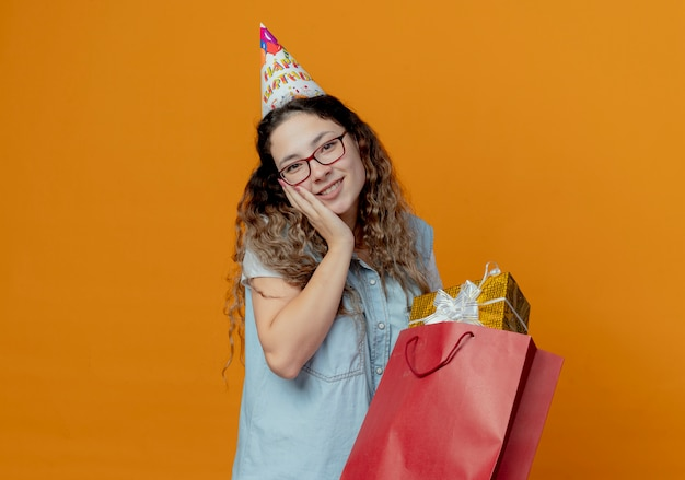 Smiling young girl wearing glasses and birthday cap holding gift boxes with bags