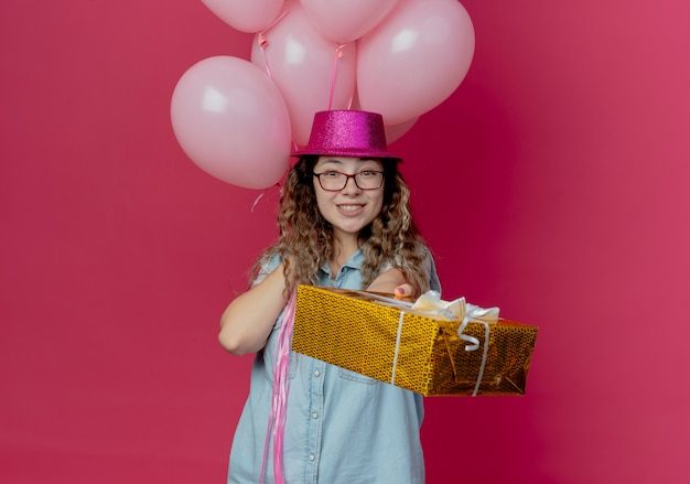 Smiling young girl wearing glasses and pink hat holding nalloons and holding out gift box to camera isolated on pink