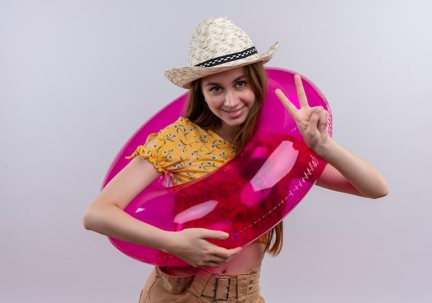 孤立した白い壁にピースサインをしている帽子と浮き輪を身に着けている若い女の子の笑顔