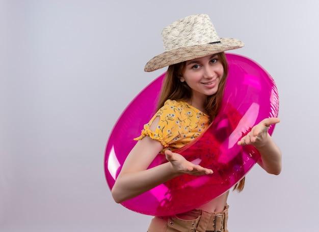 コピースペースと孤立した白い壁に空の手を示す帽子と浮き輪を身に着けている若い女の子の笑顔