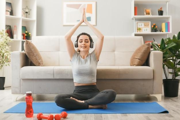 リビングルームのソファの前でヨガマットで運動するヘッドフォンを身に着けている若い女の子の笑顔