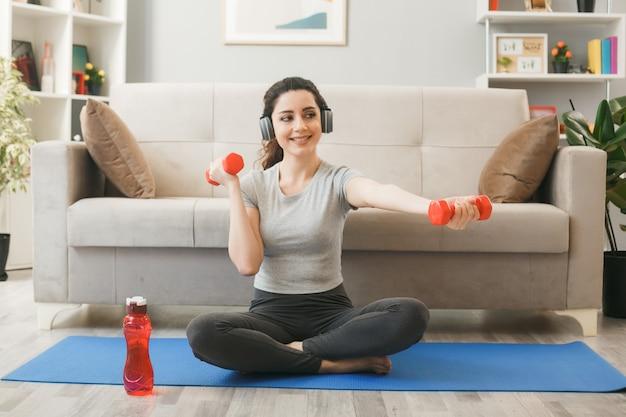 リビングルームの前のソファでヨガマットにダンベルで運動するヘッドフォンを身に着けている若い女の子の笑顔