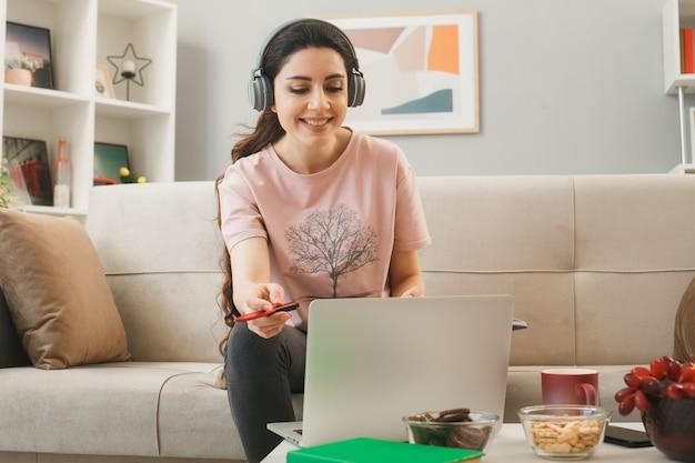 ペンを保持しているヘッドフォンを身に着けている笑顔の若い女の子は、リビングルームのコーヒーテーブルの後ろのソファに座っているラップトップを使用しました