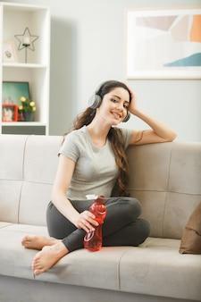 거실 소파에 앉아 물병을 들고 헤드폰을 끼고 웃고 있는 어린 소녀