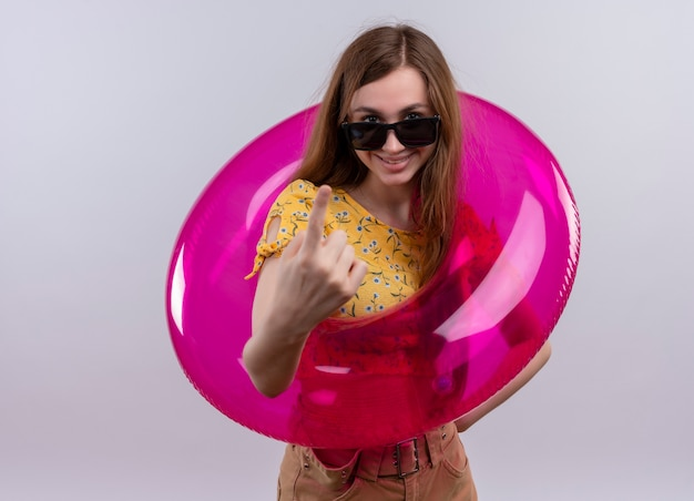 Sorridente ragazza che indossa occhiali da sole e anello di nuotata facendo venire qui gesto sulla parete bianca isolata con lo spazio della copia
