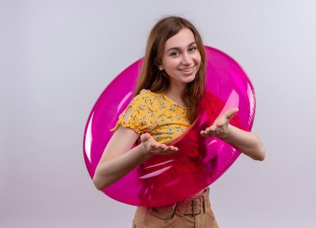 浮き輪を身に着けて、コピースペースのある孤立した白い壁に空の手を示す笑顔の若い女の子