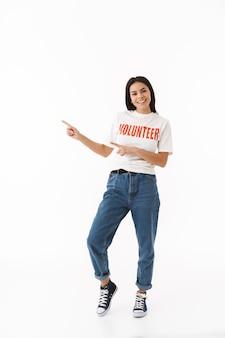 Улыбающаяся молодая девушка в футболке добровольца стоит изолированно над белой стеной, указывая пальцем на копировальное пространство