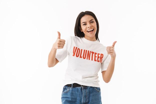 Улыбающаяся молодая девушка в футболке-добровольце стоит изолированно над белой стеной, показывает палец вверх