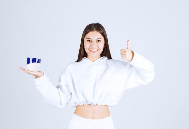 Улыбающаяся молодая девушка с чашкой и показывая большой палец вверх на бело-сером фоне.