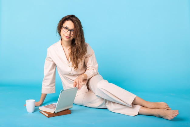 Smiling young girl with books in pajamas home wear posing while resting at home isolated on blue background studio portrait. relax good mood lifestyle concept.