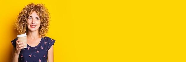 Улыбающаяся молодая девушка с вьющимися волосами держит бумажный стаканчик на желтой поверхности