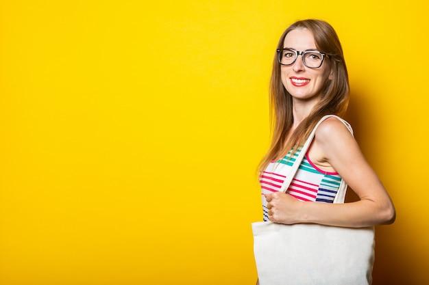 안경 웃는 어린 소녀는 그녀의 어깨에 린넨 가방을 보유하고 있습니다.