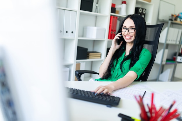 Smiling young girl with glasses in the office speaks on the phone and holds a hand on the keyboard.