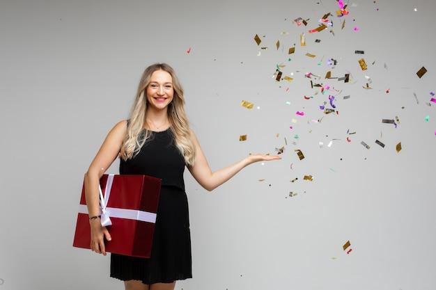 Ragazza sorridente con un grande regalo festivo che punta a mano su uno spazio vuoto con coriandoli festivi su sfondo grigio