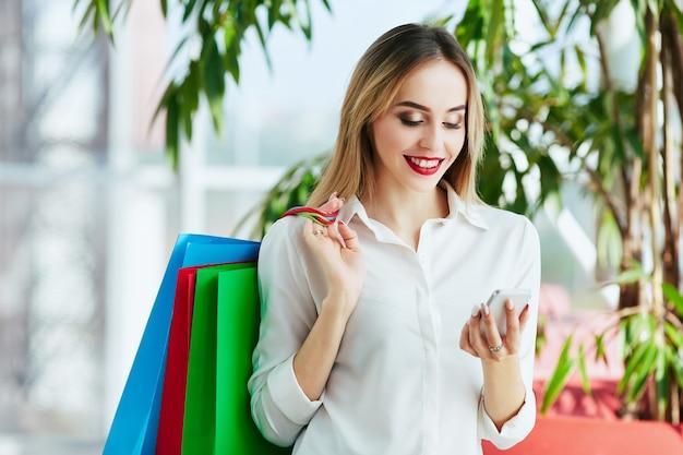 白いブラウスを着て、カラフルな買い物袋を持って立って、携帯電話、ショッピングコンセプト、コピースペースを持って、明るい茶色の髪と赤い唇を持つ若い女の子を笑顔。