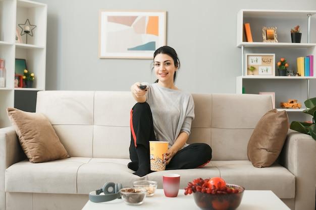 リビングルームのコーヒーテーブルの後ろのソファに座って、テレビのリモコンを保持しているポップコーンバケツと笑顔の若い女の子
