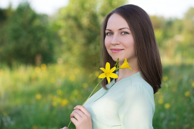 Smiling young girl with yellow flower in her hand.