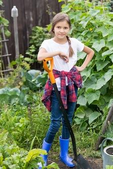 삽으로 정원에서 일하는 웃는 어린 소녀