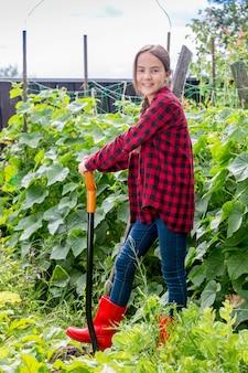 정원에서 삽으로 일하는 웃는 어린 소녀