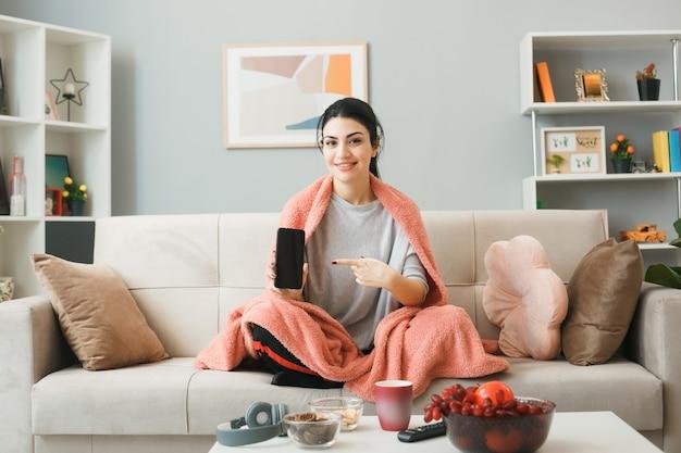 Улыбающаяся молодая девушка, завернутая в плед, и указывает на телефон, сидя на диване за журнальным столиком в гостиной